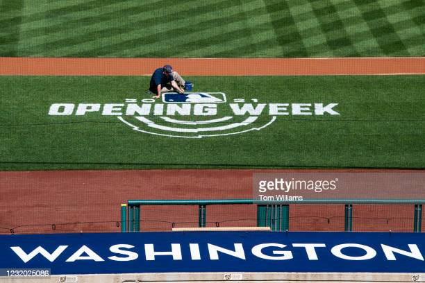 Worker paints the MLB logo on the field during a media tour of Nationals Park to explain the health and safety protocols implemented due to the...