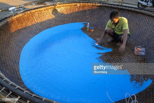 A worker paints the surface of a basket boat near Tan Quang harbor in Quang Nam province Vietnam on Wednesday June 26 2019 Fishermen are on the front...