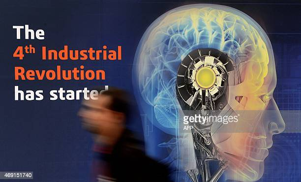 A worker passes a display lettering 'The 4th Industrial Revolution has started' prior to the opening of the Hannover Messe industrial trade fair on...
