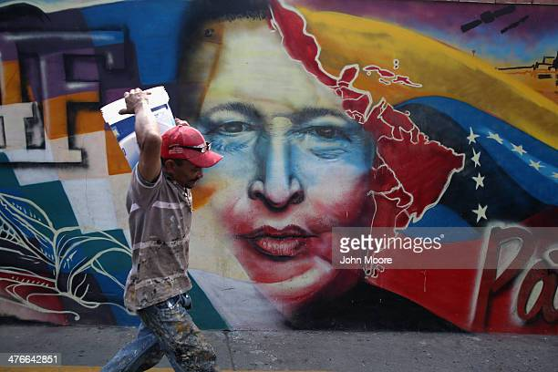 A worker passes a mural of Hugo Chavez at the military barracks where the former Venezuelan president is entombed on March 4 2014 in Caracas...