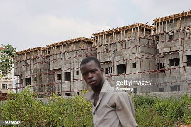 A worker passes a residential housing estate under construction in Abuja Nigeria on Wednesday Oct 21 2015 A drop in crude prices in the past year has...