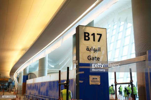 A worker passes an under construction departure gate at Abu Dhabi airport's MidField terminal during construction in Abu Dhabi United Arab Emirates...