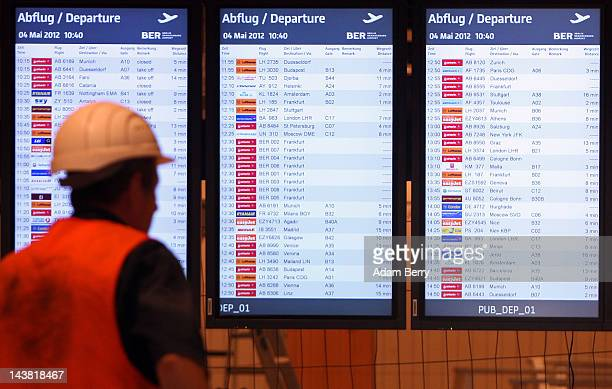 A worker passes boards displaying flight information from nearby airports as a test to make sure they are running correctly in the departures area of...
