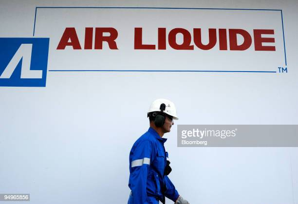 A worker passes by an Air Liquide logo at the Air Liquide hydrogen plant in Port Jerome France on Friday July 24 2009 The company announces its...