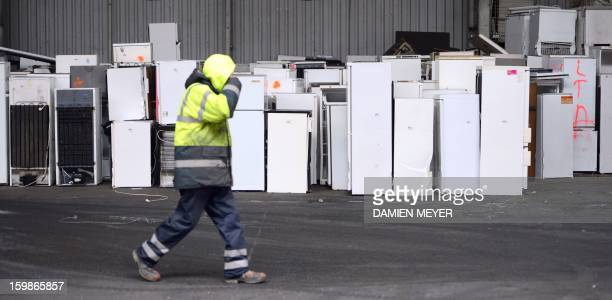 A worker passes by household appliances at Retrilog Company owned by French charity association Emmaus specialized in transport collection and...