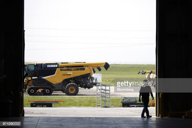 A worker passes in front of a combine harvester parked outside the CLAAS of America Inc production facility in Omaha Nebraska US on Wednesday June 6...