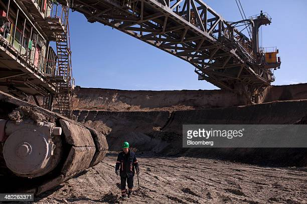 A worker passes in front of a giant excavator as its bucket wheels collect earth during lignite also known as brown coal digging operations at the...