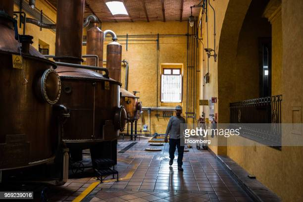 A worker passes in front of distillation tanks at the Becle SAB Jose Cuervo distillery in the town of Tequila Jalisco state Mexico on Thursday May 3...