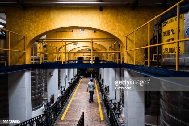 A worker passes in front of fermentation tanks at the Becle SAB Jose Cuervo distillery in the town of Tequila Jalisco state Mexico on Thursday May 3...