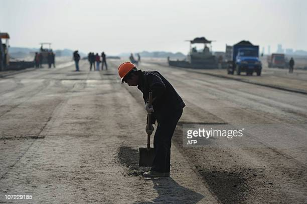A worker patches a a hole on a runway construction of the new Hefei Xinqiao International Airport in Hefei east China's Anhui province on November 30...