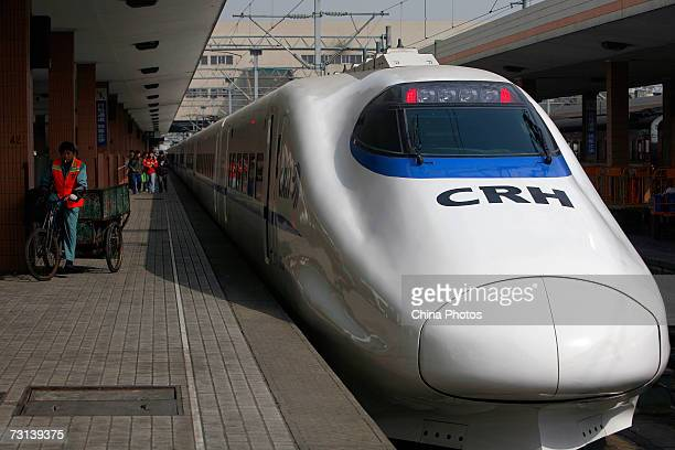 A worker pedals past a CRH 'bullet train' at Hangzhou Railway Station January 28 in Hangzhou Zhejiang Province China China's bullet train the...