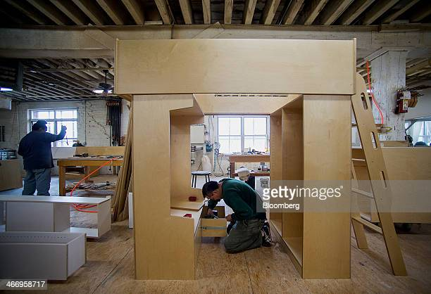 Worker Pedro Rosas right builds a drawer inside on a loft bed at Casa Kids' Red Hook facility in the Brooklyn borough of New York US on Friday Jan 31...