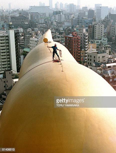 A worker perches on top of a gigantic object symbolising Japan's leading beer company Asahi Beer Co whilst cleaning up the surface 22 April The...