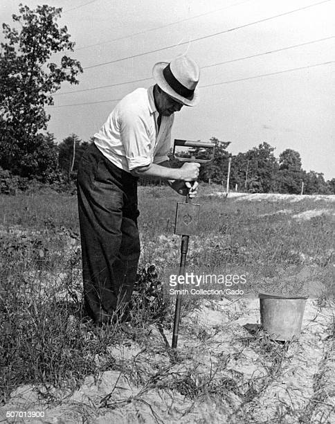 Worker performing a moisture test on soil at the United States Department of Agiculture experimental farm in Beltsville Maryland 1935 From the New...