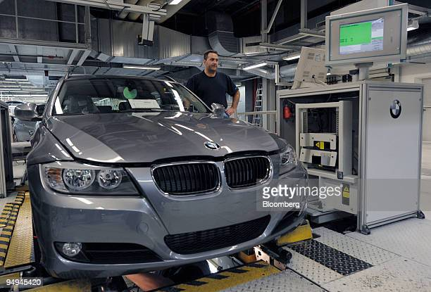A worker performs the final check of a BMW 3series automobile on the production line at the BMW factory in Munich Germany on Wednesday March 11 2009...