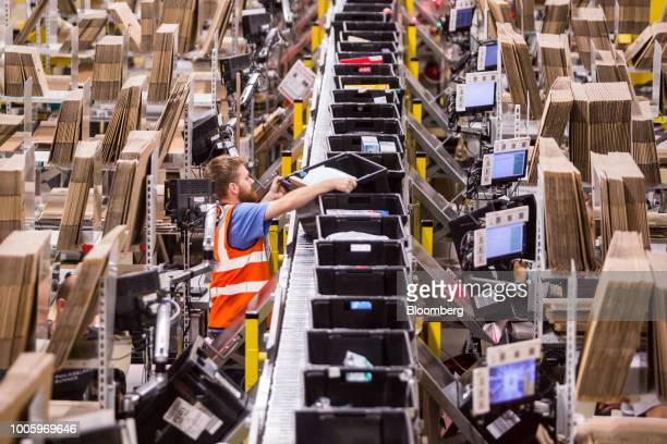 A worker picks a storage box containing a customer's order at the Amazoncom Inc fulfillment center in Passo Corese Rieti Italy on Thursday July 26...