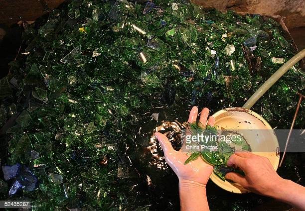A worker picks through glass fragments used to produce fiberglass at a fiberglass factory March 16 2005 in Chengdu Sichuan Province China Premier Wen...