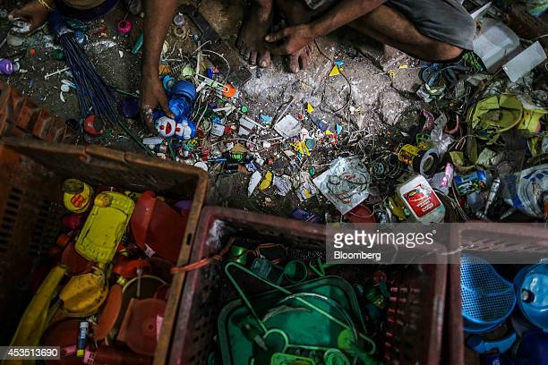 A worker picks up a Doraemon figurine as he sorts through plastic waste for recycling in the Dharavi slum area of Mumbai India on Monday Aug 11 2014...