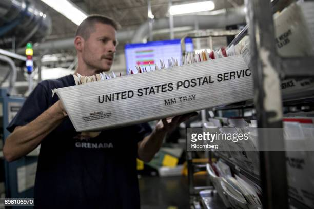 A worker places a mail tray on a cart at the United States Postal Service Suburban processing and distribution center in Gaithersburg Maryland US on...