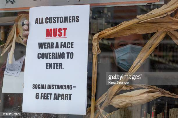 A worker places a placard on the window of a liquor store while wearing a face mask on April 10 2020 in Jersey City New Jersey On Wednesday New...