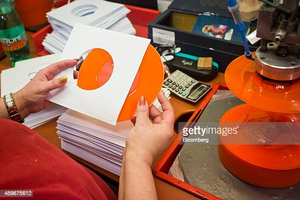 A worker places an orange colored 7' inch vinyl record into a record sleeve during the manufacturing process of vinyl records by GZ Media as at their...