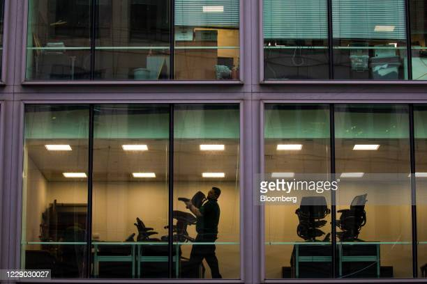 Worker places chairs on tables as he cleans an office in the City of London, U.K., on Monday, Oct. 12, 2020. The approach of Brexit has London...