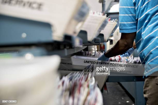 A worker places mail into a tray after being run through an advanced face cancelling machine at the United States Postal Service Suburban processing...