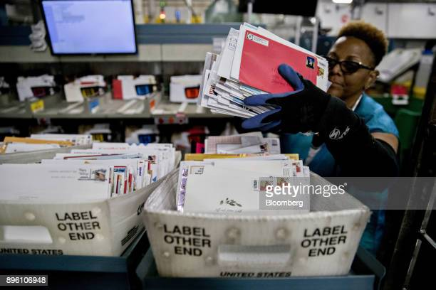 A worker places mail into a tray next to an advanced face cancelling machine at the United States Postal Service Suburban processing and distribution...