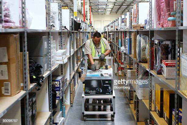 A worker places merchandise on a shelving unit at the Amazoncom Phoenix Fulfillment Center in Goodyear Arizona US on Monday Nov 16 2009 Seattlebased...