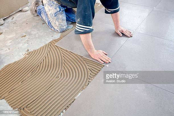 Worker places new tile on a floor