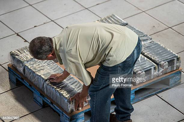 Worker places packages of coffe into a pallet that are going to be loaded into a truck to be delivered to supermarkets at Café Primavera Itapira...
