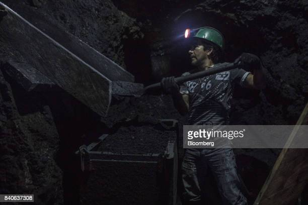 A worker places rocks into a wagon while mining for emeralds inside a pit in Muzo Colombia on Friday Aug 4 2017 Colombia is the world's largest...