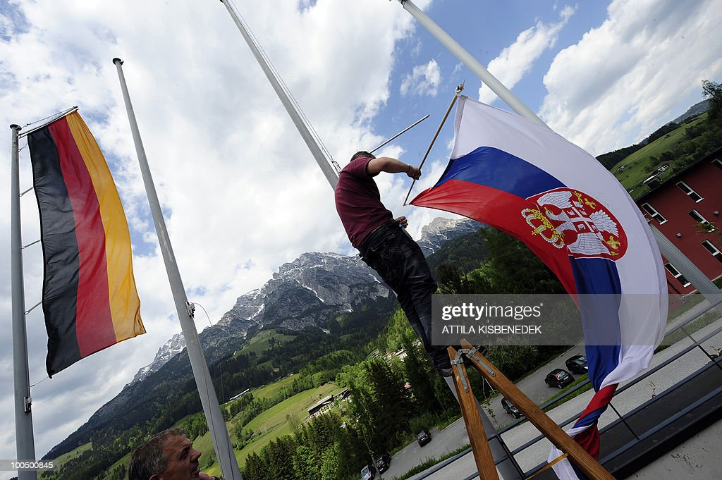A worker places the Serbian flag outside