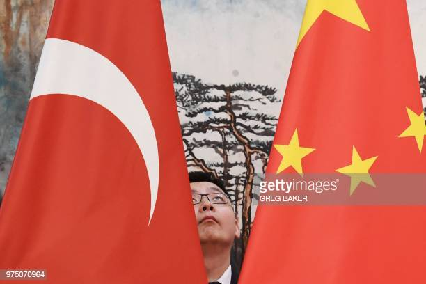 Worker places the Turkish and Chinese flags before a meeting between the Turkey's Foreign Minister Mevlut Cavusoglu and China's Foreign Minister Wang...