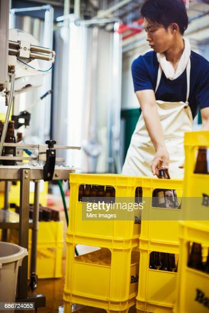 Worker placing beer bottles into yellow crates in a brewery.