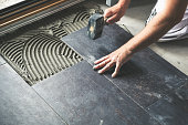 Worker placing ceramic floor tiles