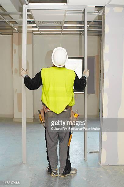 Worker placing door frame on site