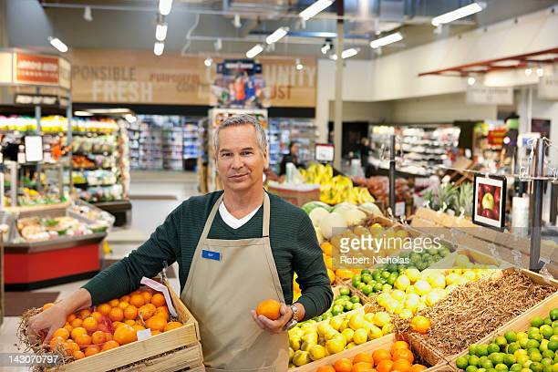 Worker placing oranges in supermarket display