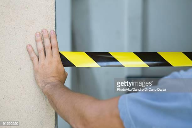 Worker placing safety tape across doorway