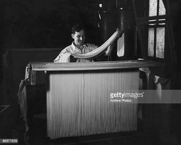 A worker placing spaghetti on a drying rack before it is transferred to a dryer Italy circa 1955