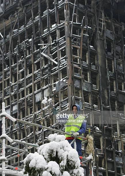 A worker plays with snow in front of the Windsor building destroyed one week ago by fire in Madrid 23 February 2005 AFP PHOTO CHRISTOPHE SIMON