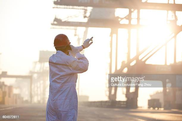 Worker pointing at crane in port