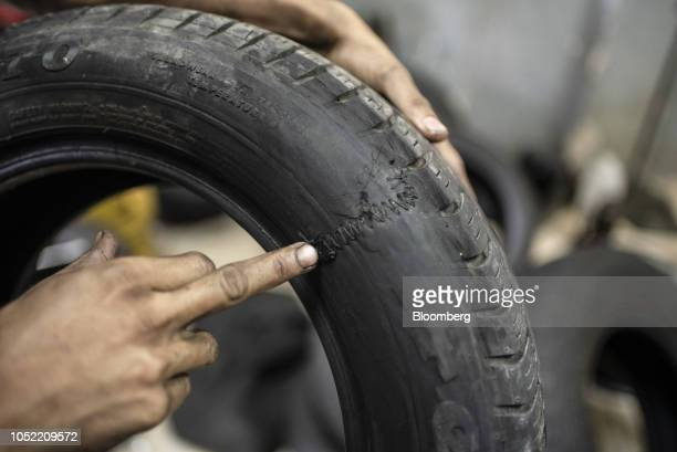 A worker points to stitching used to repair a damaged tire at a shop in Caracas Venezuela on Wednesday Aug 29 2018 Hyperinflation and scarcity have...