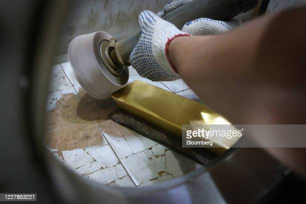 Worker polishes a 12.5 kilogram gold ingot at the Uralelectromed Copper Refinery, operated by Ural Mining and Metallurgical Co. , in Verkhnyaya...