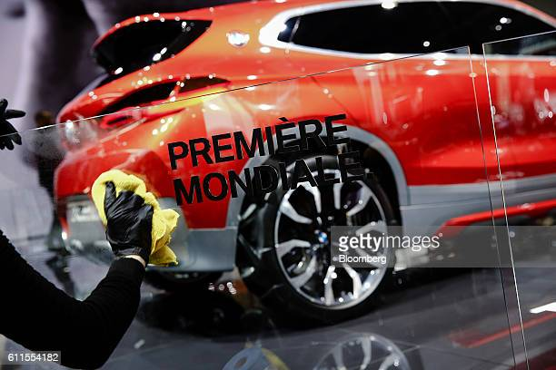 Worker polishes a glass panel on the BMW stand as a new BMW X2 concept electric automobile, manufactured by Bayerische Motoren Werke AG, sits on...