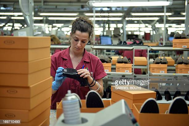 Worker polishes a shoe in the factory of the Italian shoes and luxury leather goods Tod's on May 28, 2013 at the headquarters of the company in...