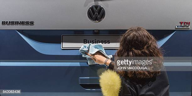 A worker polishes a Volkswagen multivan on display during German carmaker Volkswagen shareholders' annual general meeting on June 22 2016 in Hanover...