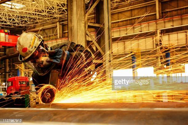 A worker polishes an oil pipe at a factory in Qingdao in China's eastern Shandong province on February 28 2019 China's manufacturing activity shrunk...