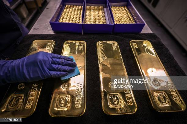 Worker polishes gold bullion bars at the ABC Refinery in Sydney on August 5, 2020. - Gold prices hit 2,000 USD an ounce on markets for the first time...