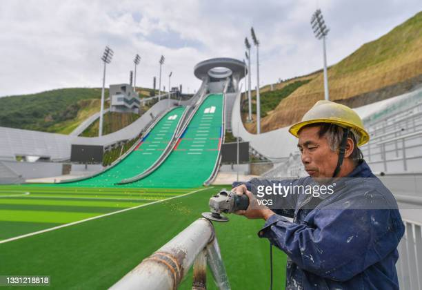 Worker polishes railing at the national ski jumping center which is under construction in Chongli district for the Beijing 2022 Winter Olympics on...